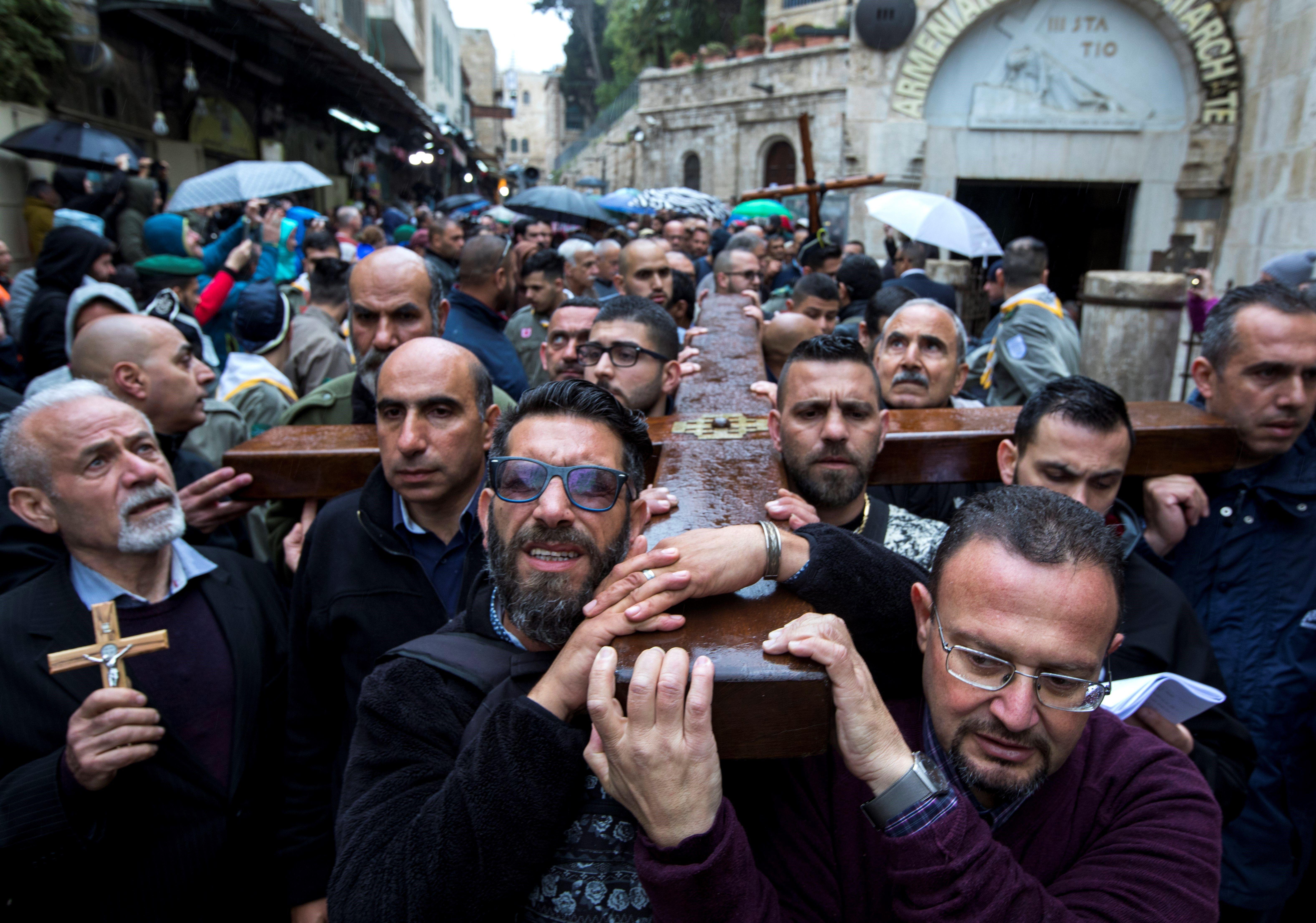 Cristianos cargan con una cruz de madera en la Vía Dolorosa, misma ruta por la que Jesucristo llevó a...