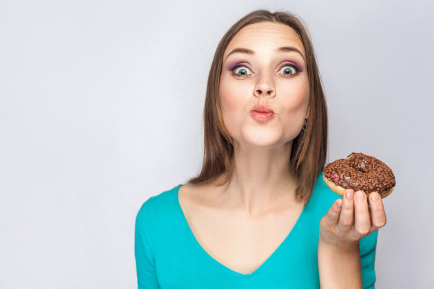 Portrait of beautiful girl with chocolate donuts. eating and looking at camera with funny face. studio...