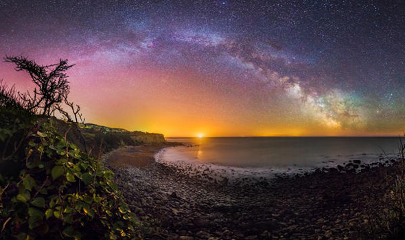 ISLE OF WHITE, GREAT BRITAIN - MAY 13: A view of the Milky Way taken by Chad Powell on a DSLR camera on May13, 2015. Taken at Mount Bay, St Lawrence just minutes before the moon crept above the horizon and washed out the sky. The bright light prominent in the very centre of the image, often mistaken as the sun in my images is a large container ship, often anchored in the distance, ready to dock at Portsmouth/Southampton harbour.   LIGHTS from the Milky Way dazzle above the Isle of White in these rarely seen British sky-scapes. Chad Powell captured images of spectacular light patterns above the familiar beach scenes of England?s largest island. The 23-year-old used a DSLR camera to enhance the Milky Way from the white strip visible to the naked eye into an explosion of colourful lights. The graphic designer from Ventnor, Isle of Wight, used the local architecture, coves and plant life of the island in the foreground of his photographs to create a contrast with the dramatic sky. Wheat fields, night daisies and a medieval lighthouse are some of the scenes Chad captures against the startling natural light displays.  PHOTOGRAPH BY Chad Powell / Barcroft Media  UK Office, London. T +44 845 370 2233 W www.barcroftmedia.com  USA Office, New York City. T +1 212 796 2458 W www.barcroftusa.com  Indian Office, Delhi. T +91 11 4053 2429 W www.barcroftindia.com
