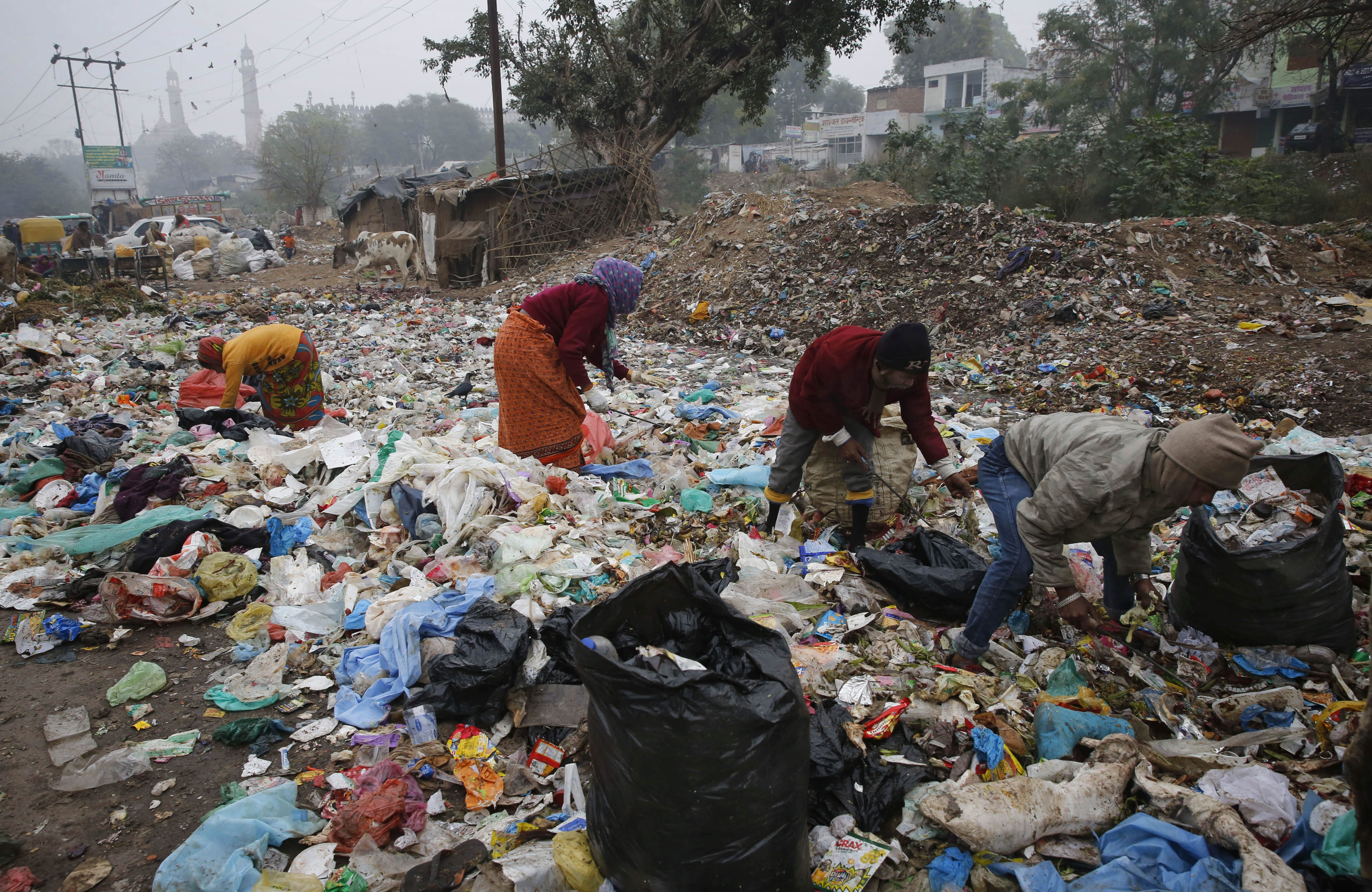 In this Jan. 21, 2016 file photo, Indian rag pickers look for reusable materials at a garbage dump littered...