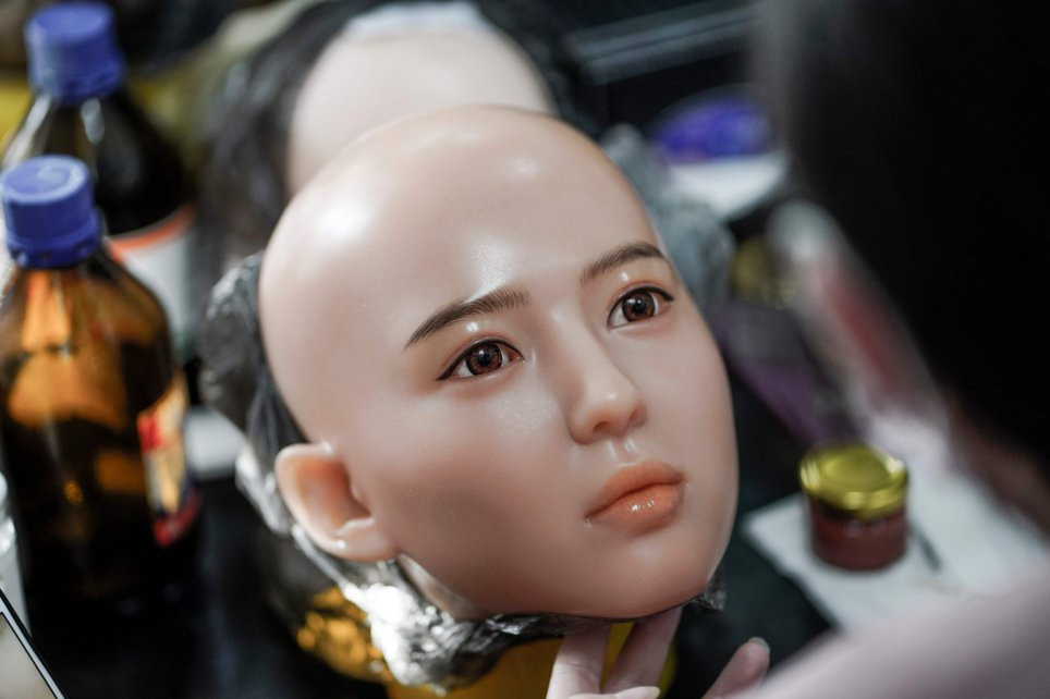 This photo taken on February 1, 2018 shows a worker painting the face of a silicone doll at a factory...