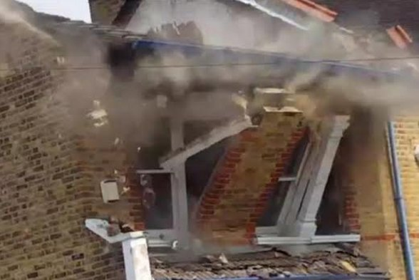 The house caught at the moment of collapse.