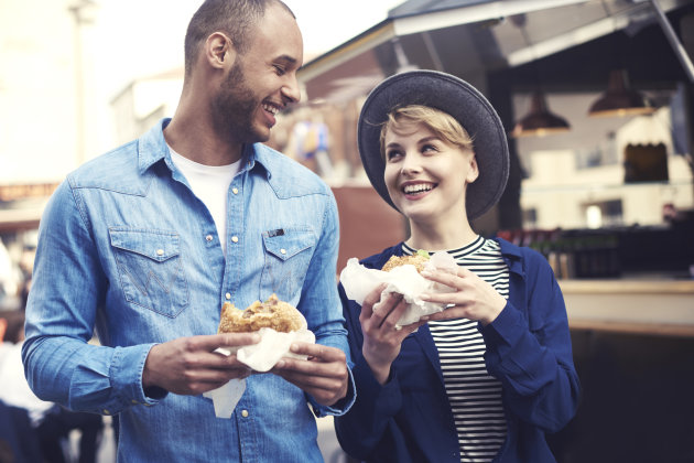 Cheerful couple trying the best hamburgers in the