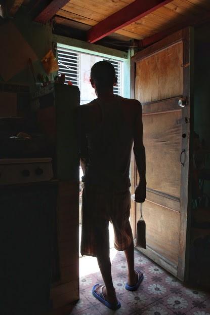 Wilson dans l'embrasure de la porte principale (et la seule) de son appartement. À la main, un sac de...