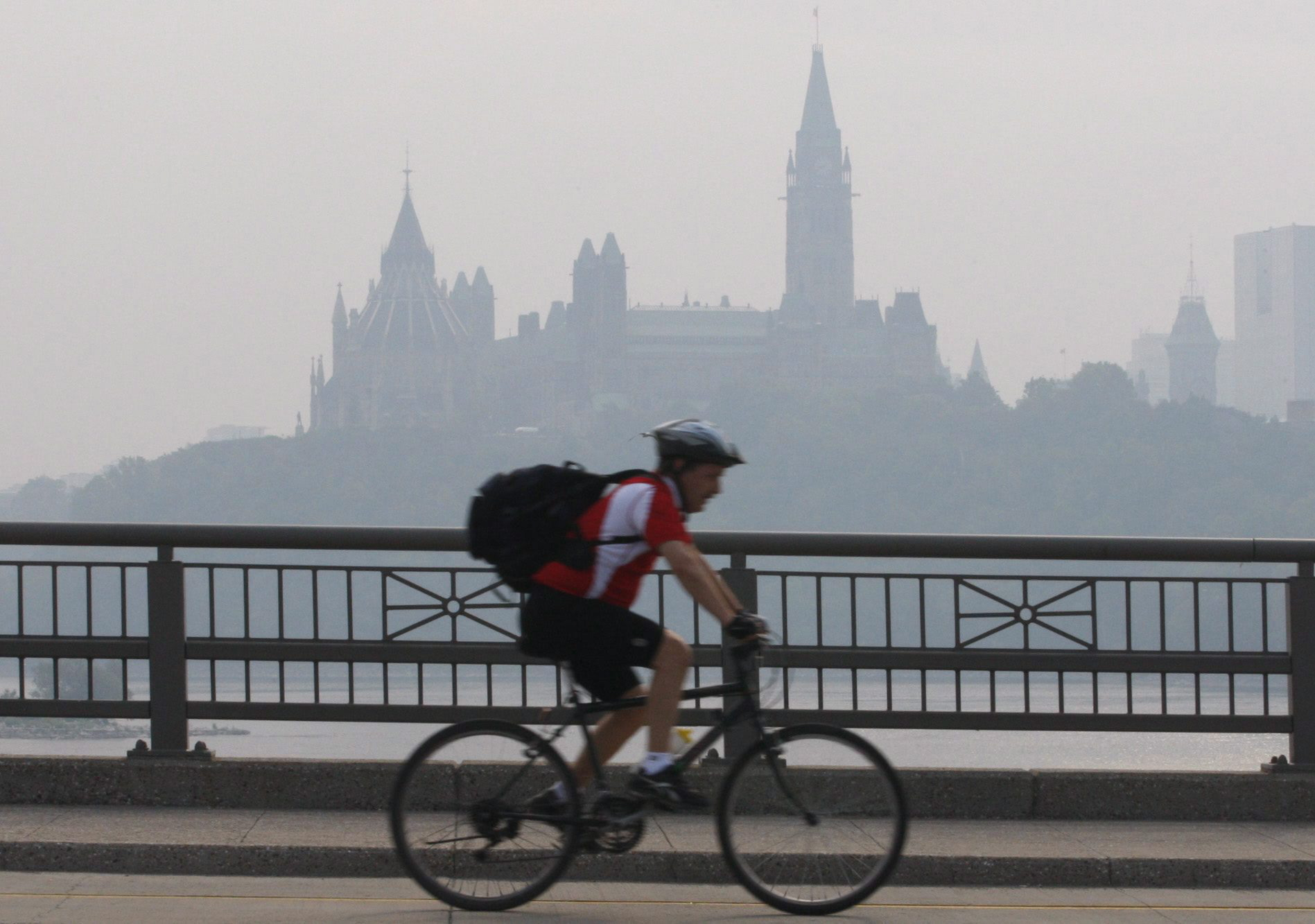 A cyclist make his way across a bridge into Ottawa as the Parliament buildings are seen through haze...