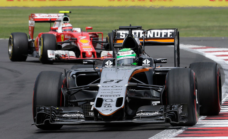 Force India's Nico Hulkenberg of Germany and Ferrari's Kimi Raikkonen of Finland (rear) compete.