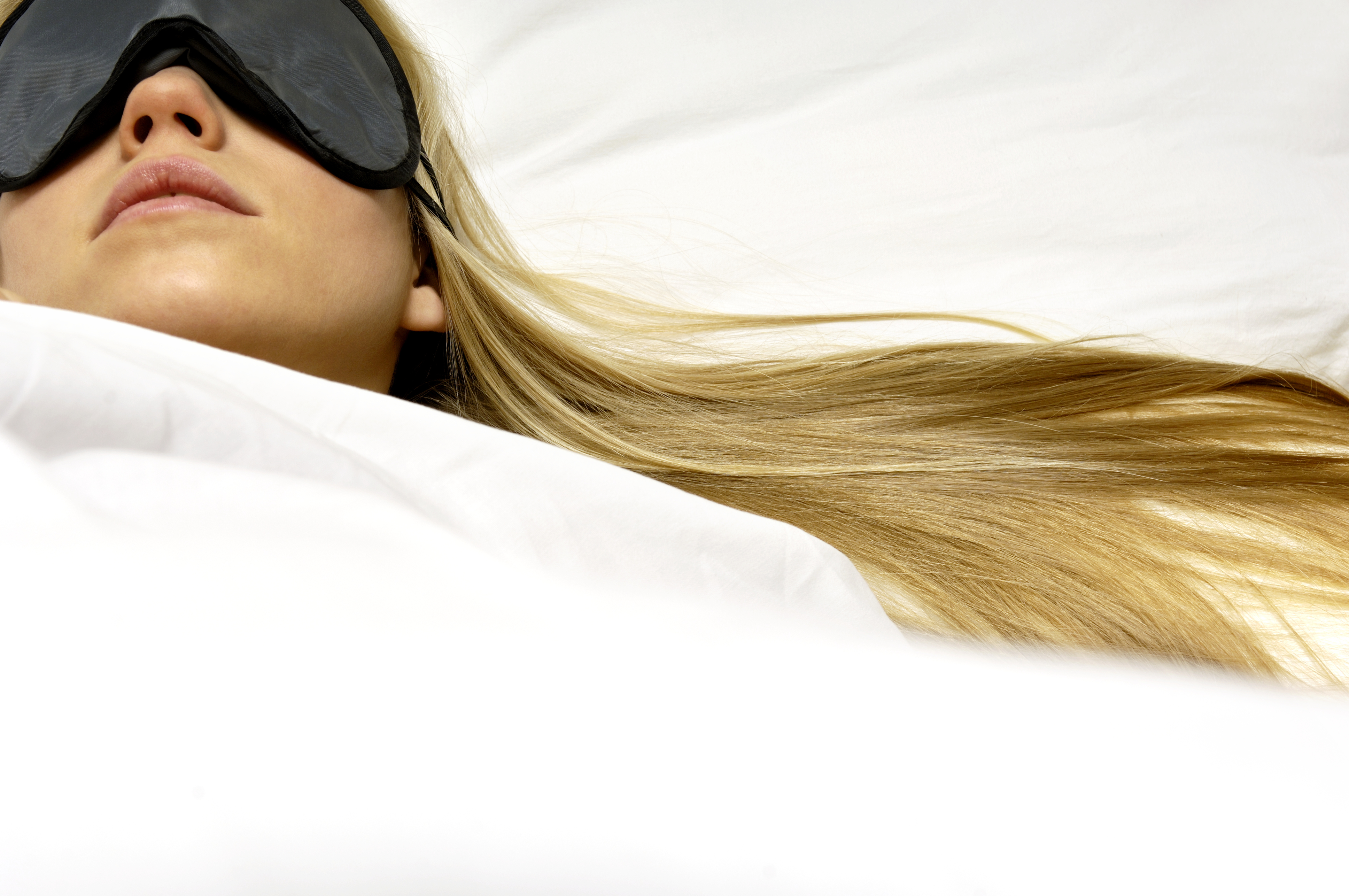 Young woman sleeping in bed, wearing sleep mask, close-up