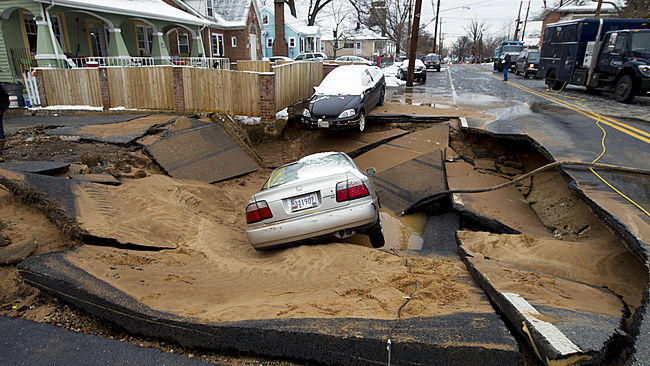 Cars swallowed by a sinkhole that occurred after a water main break in Bladensburg, Md., Tuesday, Jan. 27, 2015. A water main break caused a sinkhole in a suburban Washington, D.C. neighborhood, swallowing up a family's car just after they escaped in Bladensburg Maryland on Tuesday morning. (AP Photo/Jose Luis Magana)