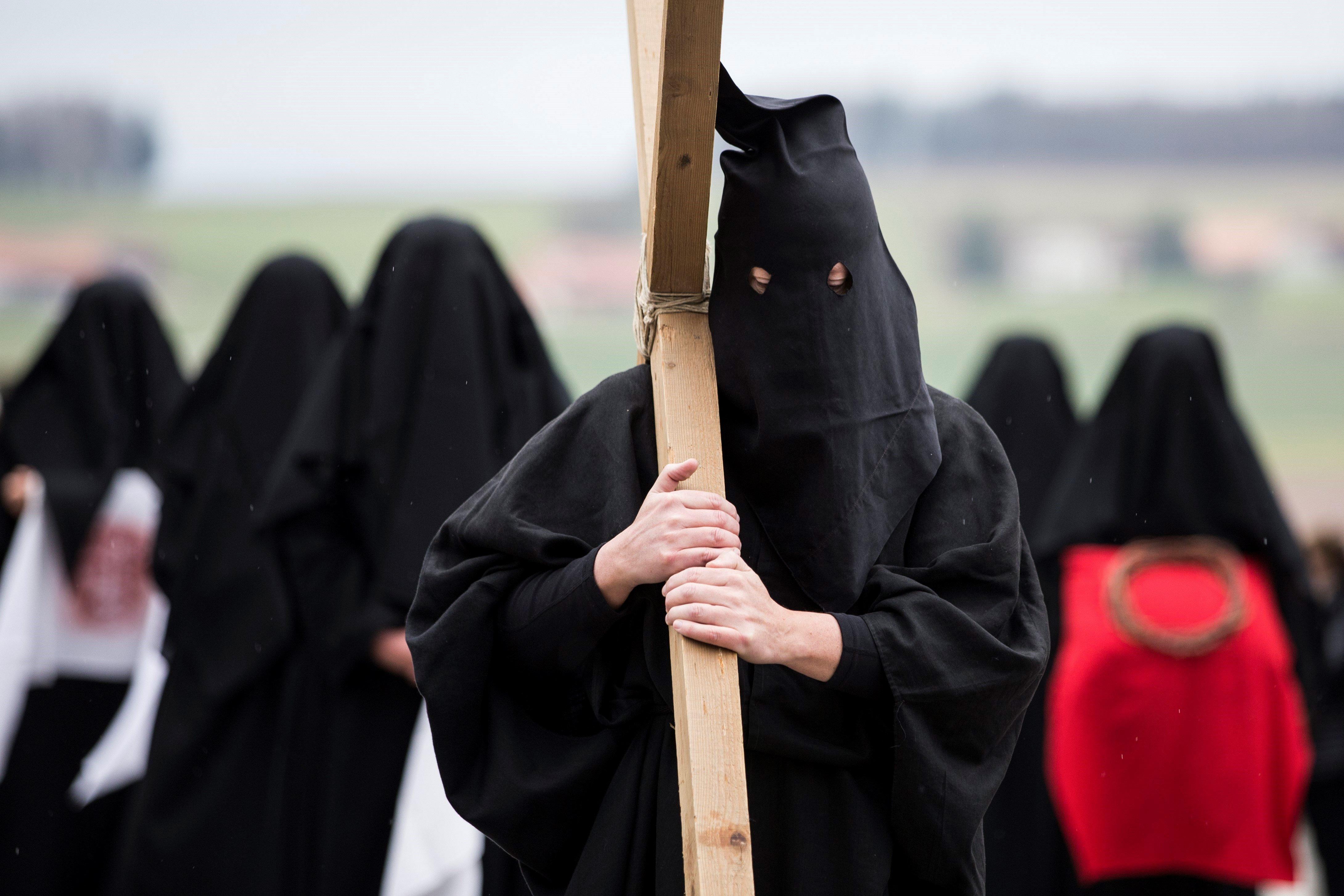 """Un portador de la cruz es seguido por las llamadas """"les Pleureuses"""" o mujeres de luto, tapadas..."""