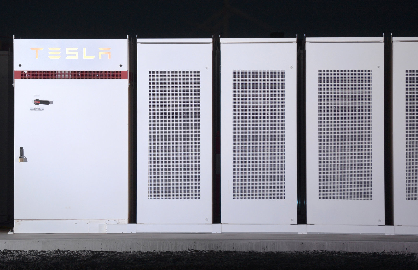 Tesla Inc. Powerpacks that will be used to form the world's largest lithium-ion battery stand on display at the Hornsdale wind farm, operated by Neoen SAS, near Jamestown, South Australia, on Friday, Sept. 29, 2017. Against a backdrop of wind turbines 150 miles (241 kilometers) north of Adelaide, Tesla Chief Executive Officer Elon Musk announced a contract to build the world's largest lithium-ion battery system had been signed with South Australia's power distributor, triggering a 100-day self-imposed deadline to install the electricity storage system. Photographer: Carla Gottgens/Bloomberg via Getty Images