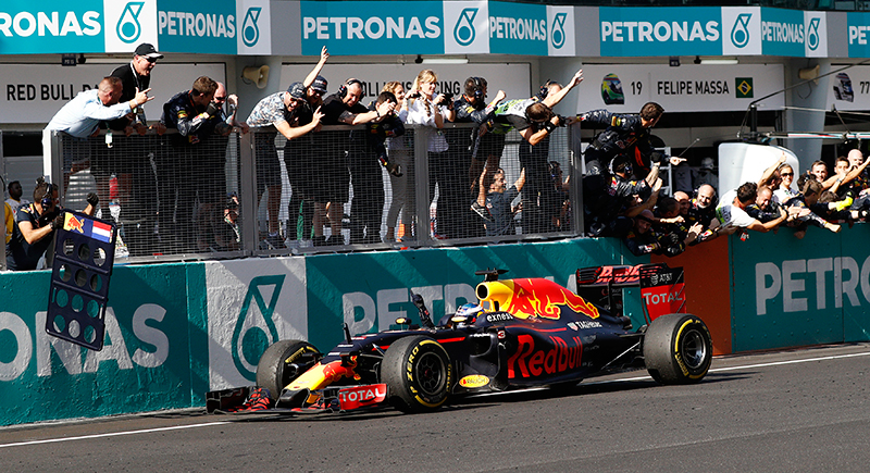 Red Bull driver Daniel Ricciardo of Australia drives past his pit crew after crossing the finish line to win the Malaysian Formula One Grand Prix at the Sepang International Circuit in Sepang, Malaysia, Sunday, Oct. 2, 2016.