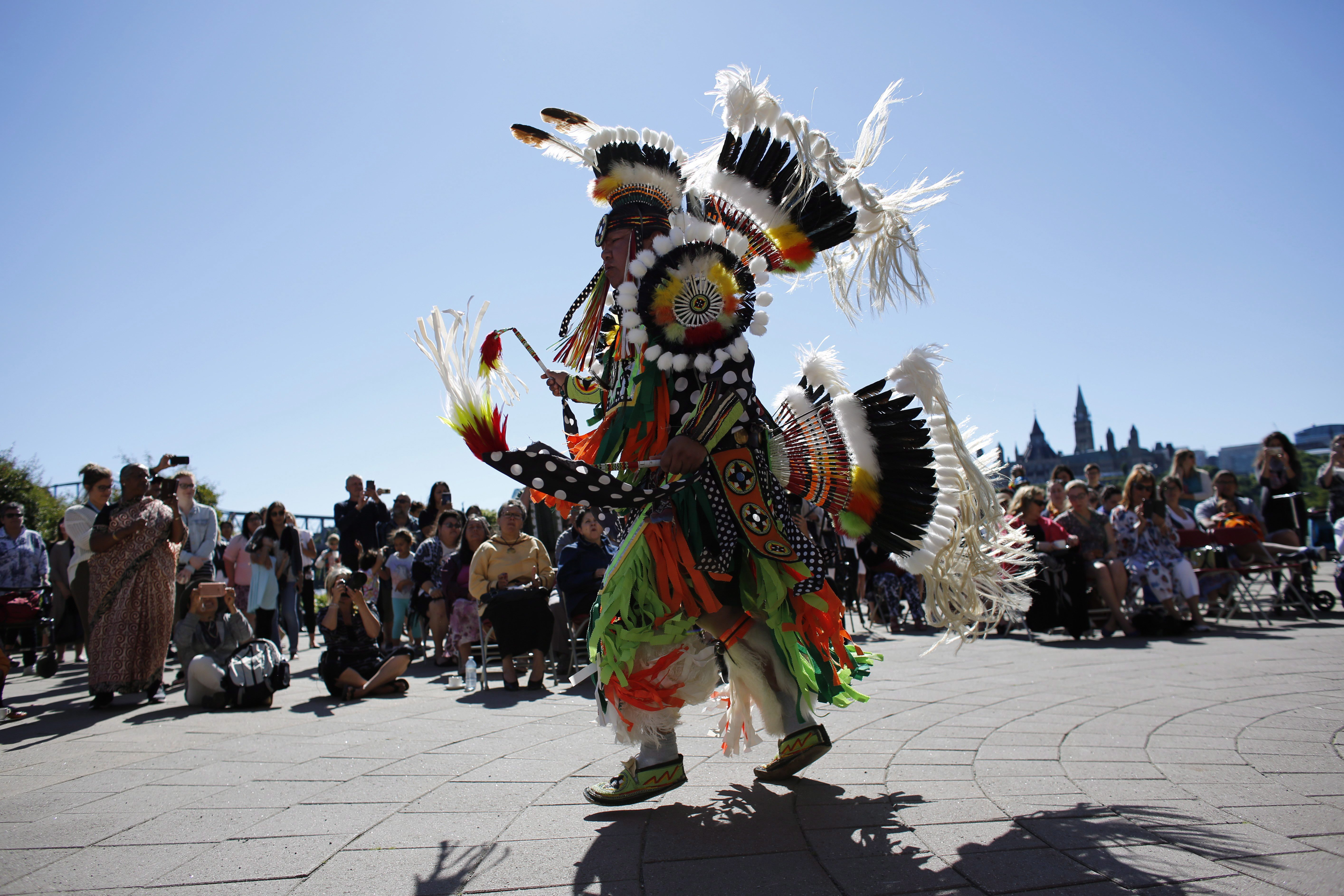 A traditional dance is performed on National Indigenous Peoples Day behind the Canadian Museum of History...