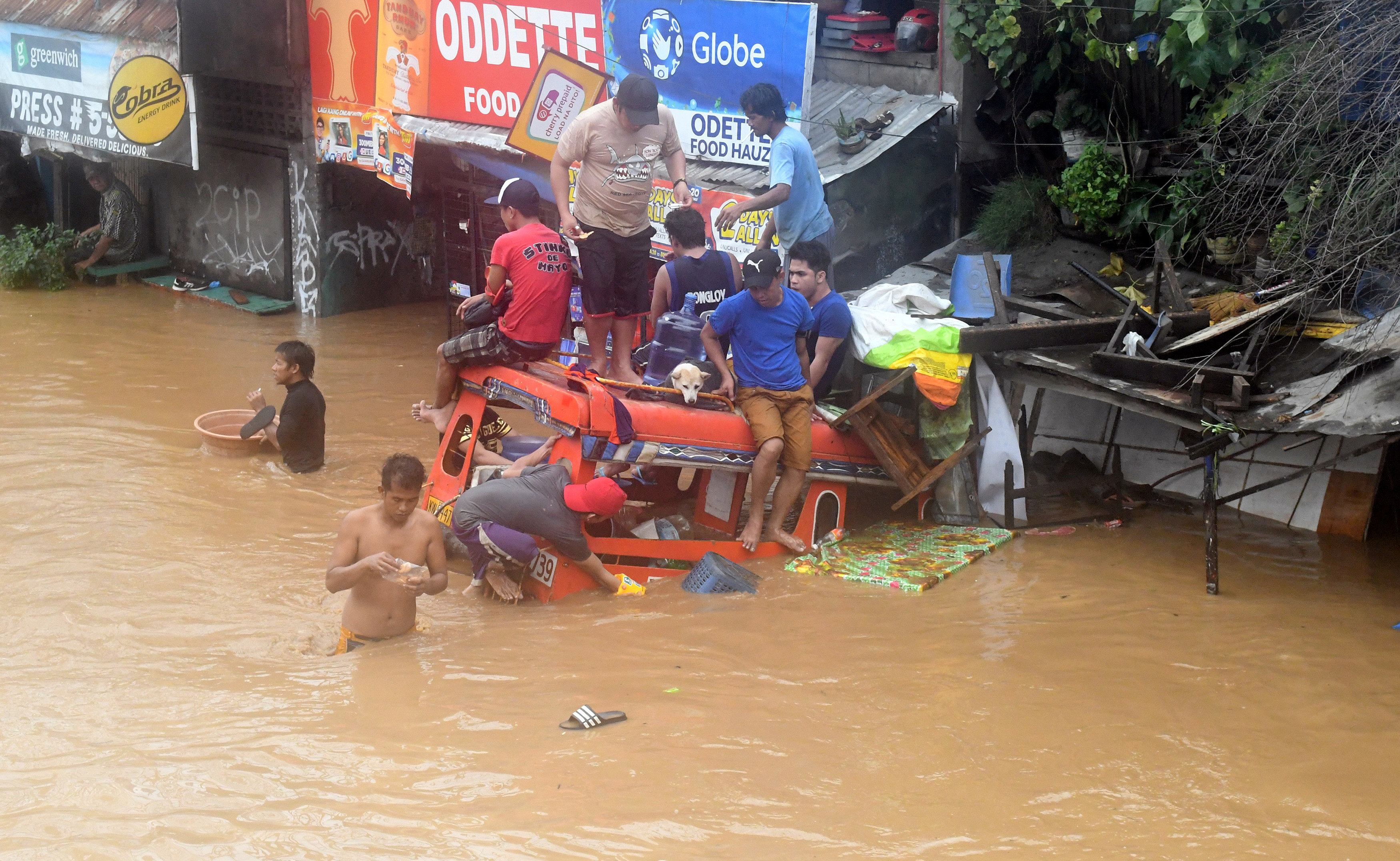 Residents are seen on the top of a partially submerged vehicle along a flooded road in Cagayan de Oro...