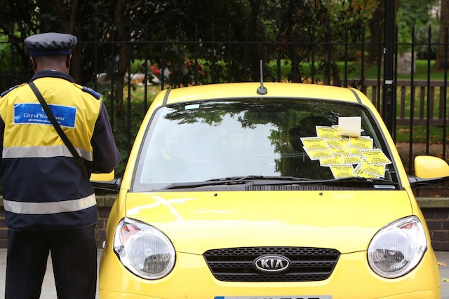 A traffic warden stands beside a car in central London which has been ticketed as part of a new T-Mobile advert where the brand has handed out thousands of pounds in £5, £10, £20 and £50 notes inside imitation parking fines on cars in and around the Capital. PRESS ASSOCIATION Photo. Issue date: Tuesday September 13, 2011. T-Mobile secretly filmed the reactions from unsuspecting members of the public for a new TV advert which launches on Friday night 9.15pm on Channel 5. Photo credit should read: Geoff Caddick/PA