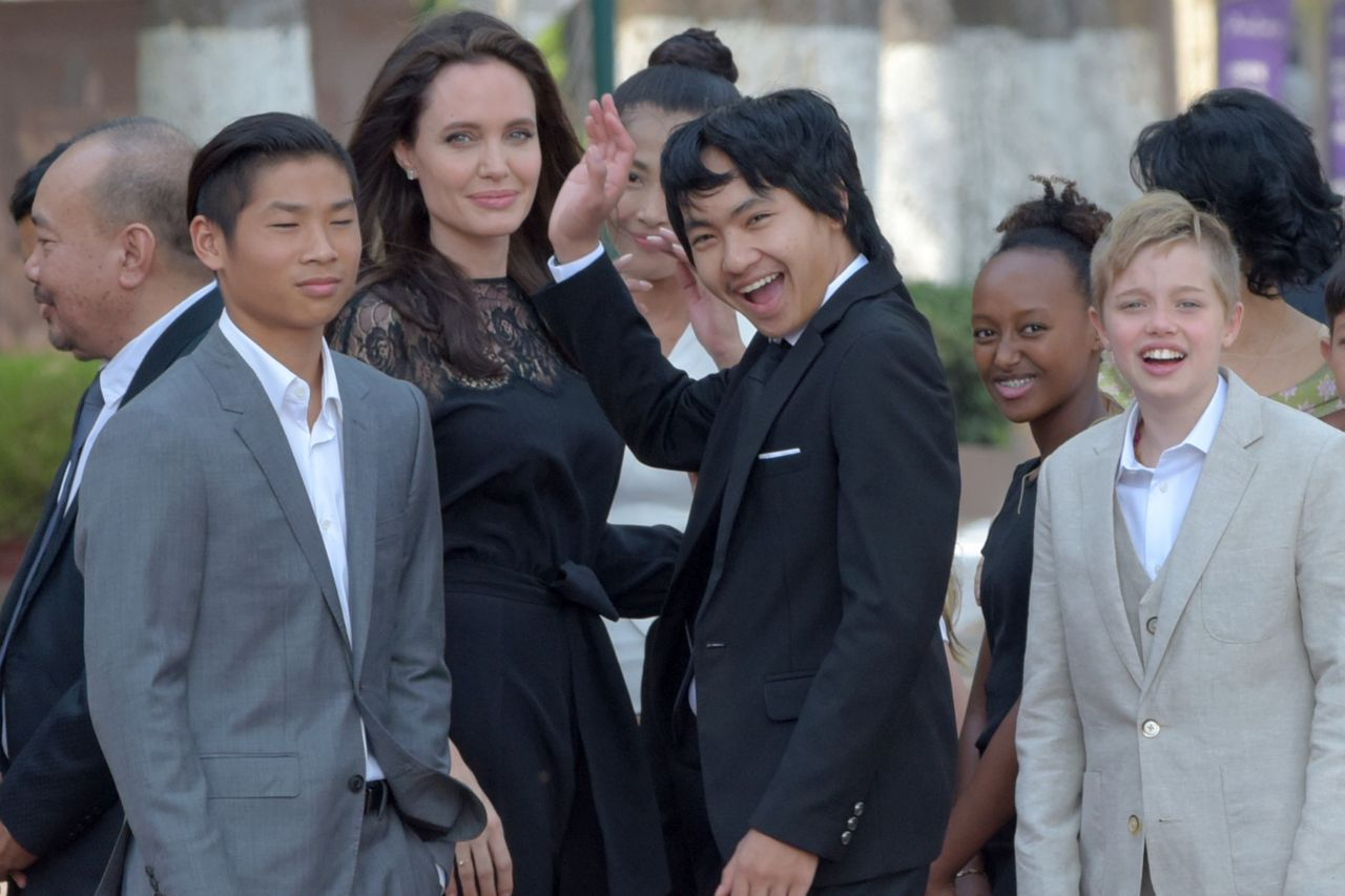 Hollywood star Angelina Jolie (3rd L) and her children including Maddox Jolie-Pitt (C) gesture to media in front of the royal residence for a meeting with Cambodian King Norodom Sihamoni in Siem Reap on February 18, 2017.  Angelina Jolie will unveil her new film on the horrors of the Khmer Rouge era on February 18 at the ancient Angkor Wat temple complex in Cambodia, a country the star shares a deep affinity with through her adopted son Maddox. / AFP / TANG CHHIN SOTHY        (Photo credit should read TANG CHHIN SOTHY/AFP/Getty Images)