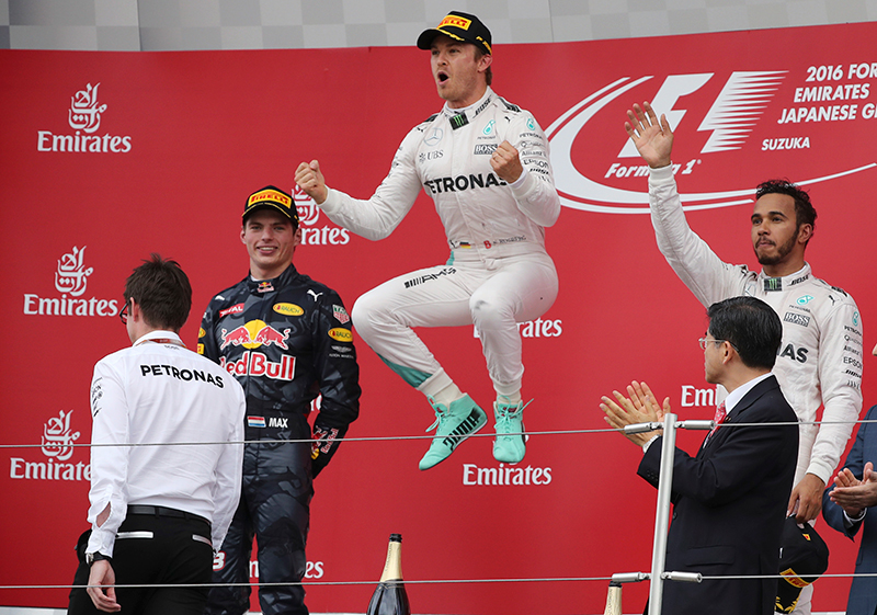 Mercedes driver Nico Rosberg, centre, of Germany celebrates on the podium after winning the Japanese Formula One Grand Prix at the Suzuka International Circuit in Suzuka, Japan, Sunday, Oct. 9, 2016. Red Bull driver Max Verstappen of the Netherlands was second and Mercedes driver Lewis Hamilton, right, of Britain third.