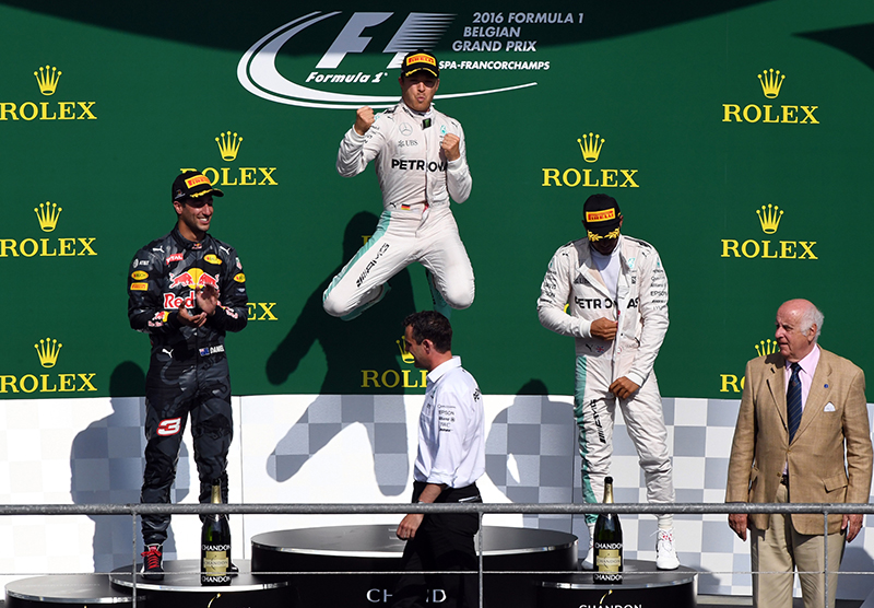 Mercedes driver Nico Rosberg of Germany, center, winner, celebrates on the podium with Red Bull driver Daniel Ricciardo of Australia, left, second place and Mercedes driver Lewis Hamilton of Britain, third place, at the Belgian Formula One Grand Prix in Spa-Francorchamps, Belgium, Sunday, Aug. 28, 2016