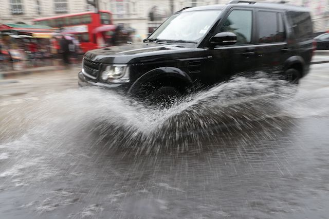 A car drives through a puddle in central London, as heavy rain and grey skies have marred the astronomical beginning of summer.