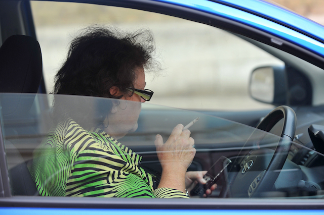 A driver using a mobile phone and smoking while waiting at traffic lights in London.