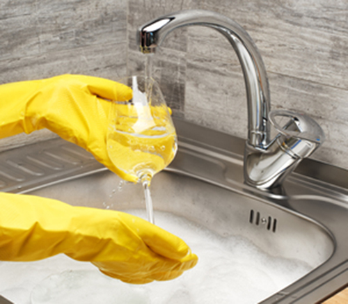 80674783 - close up of female hands in yellow protective rubber gloves washing wine glass under running...