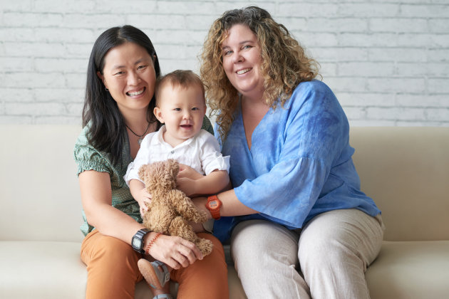 Happy multi-ethnic female couple with their adorable baby