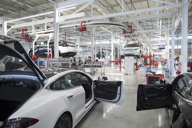 The front doors of Tesla Model X sports utility vehicles (SUV) sit open during assembly for the European market at the Tesla Motors Inc. factory in Tilburg, Netherlands, on Friday, Dec. 9, 2016. A boom in electric vehicles made by the likes of Tesla could erode as much as 10 percent of global gasoline demand by 2035, according to the oil industry consultant Wood Mackenzie Ltd. Photographer: Jasper Juinen/Bloomberg
