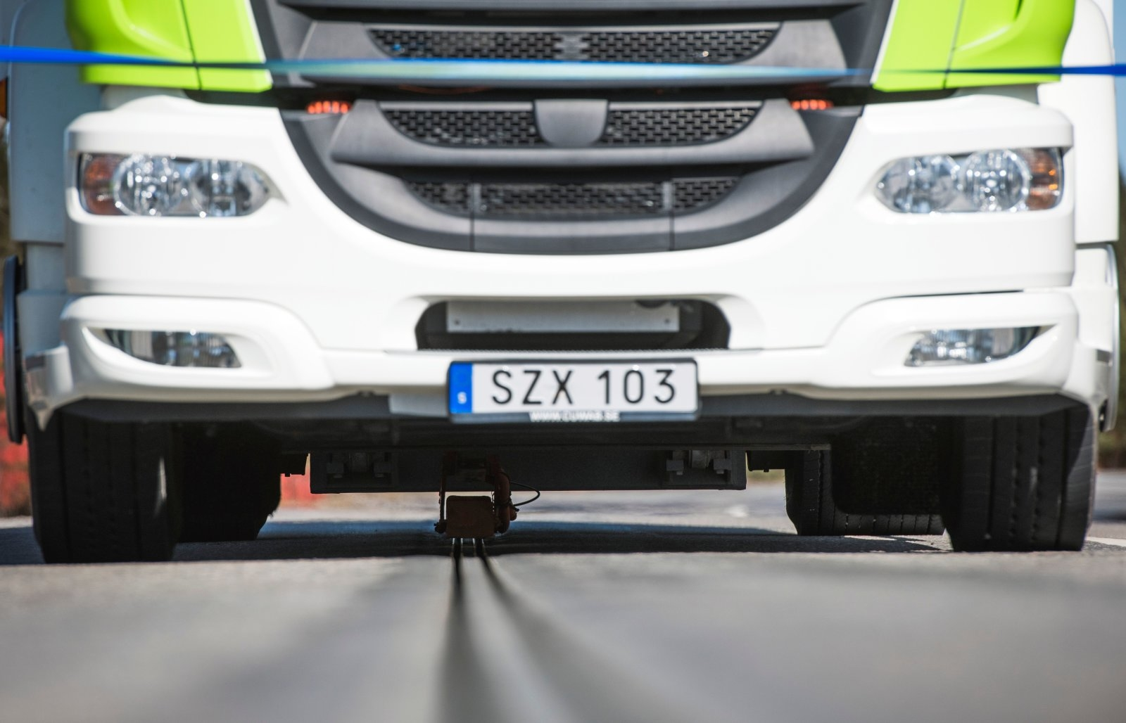 """An all-electric truck is attached to the first """"eRoad"""" of its kind, an approximately two-kilometer-long electrified road on April 11, 2018 at Arlanda airport, north of Stockholm.  This eRoadArlanda is an example of a sustainable and cost-effective solution to enable the electrification of existing commercial roads. The electrified road, a Swedish innovation, is the first of its kind in the world and allows both commercial and passenger vehicles to be recharged while driving.   / AFP PHOTO / Jonathan NACKSTRAND        (Photo credit should read JONATHAN NACKSTRAND/AFP/Getty Images)"""