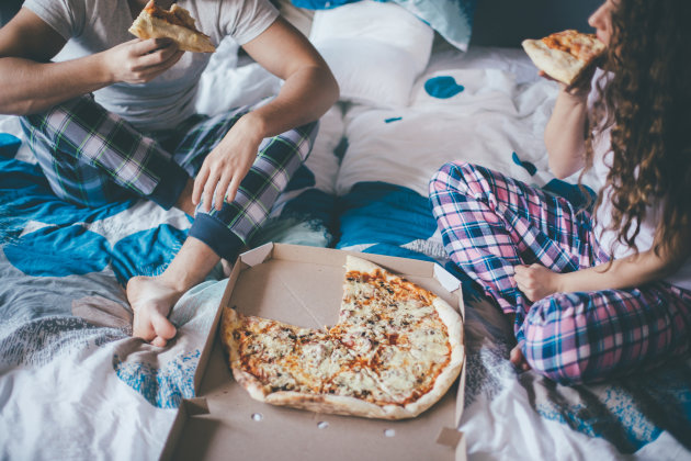 Couple having pizza in the bed in