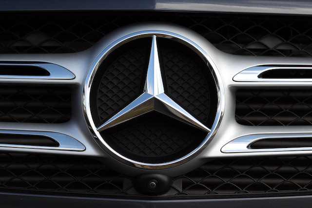 General view of a Mercedes car badge on the front grill of a car