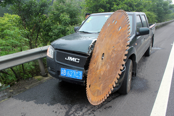 Mandatory Credit: Photo by Imaginechina/REX Shutterstock (4850359a) The car with the circular saw blade sticking out of it Circular saw blade slices into car after falling off truck, Chongqing, China - 17 Jun 2015 A man in western China had a close shave after his car was hit by a massive circular saw blade while he was driving along the road. The motorist was driving to Chongqing when he heard a bang come from the opposite lane before spotting a huge circular bouncing through the bushes of the central reservation. The blade then smashed into the front of his vehicle, slicing around 50cm into the bonnet. Highway police said another truck had crashed in the opposite lane and the blade had been thrown off the vehicle and into the road.