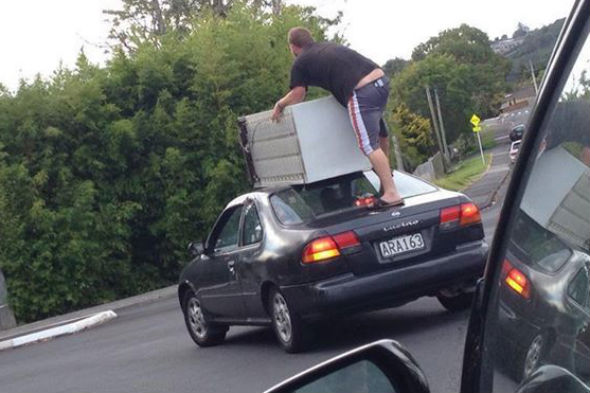 New Zealanders transport fridge on top of car