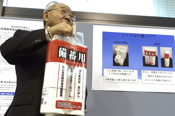 Government official Toshiyuki Hashimoto holds up a pack of toilet paper