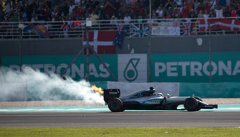 Flames and smoke pour from the rear of Mercedes driver Lewis Hamilton of Britain's car during the Malaysian Formula One Grand Prix at the Sepang International Circuit in Sepang, Malaysia, Sunday, Oct. 2, 2016