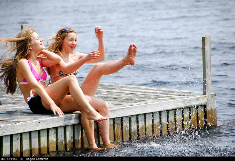 sisters 13 and 18 kicking up water while sitting on dock at