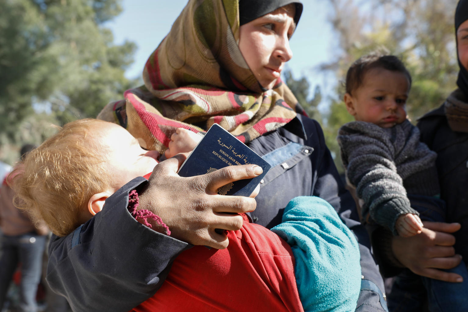 On 20 March 2018 in Adra in eastern Ghouta in the Syrian Arab Republic, a woman carries a child at the...