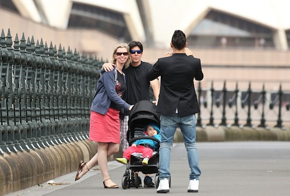 SYDNEY, AUSTRALIA - MARCH 17:  Formula 1 driver Lewis Hamilton of Great Britain and Mercedes GP takes a photo of a family under the Sydney Harbour Bridge with the Sydney Opera House in the background on March 17, 2015 in Sydney, Australia.  (Photo by El Pics/GC Images)