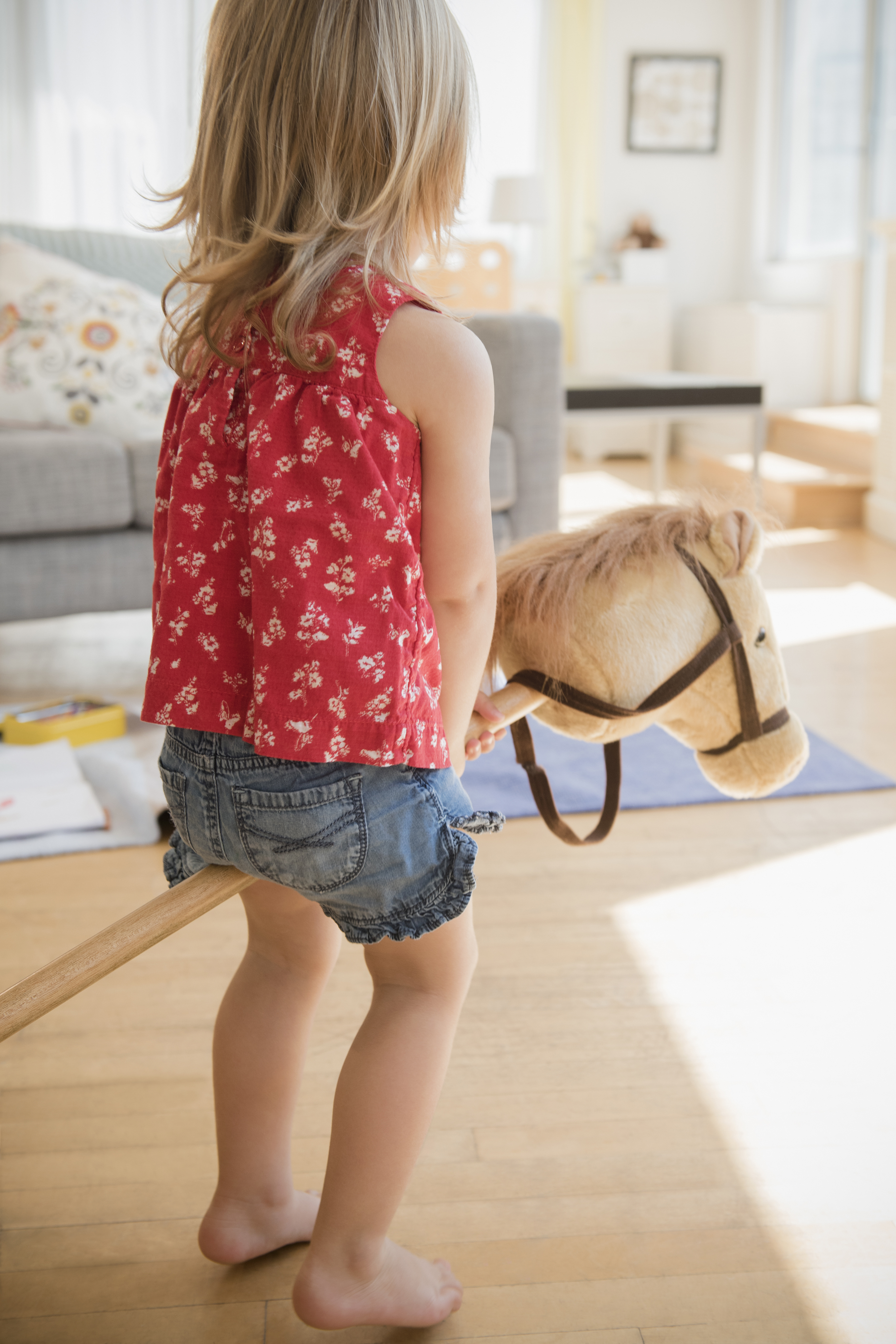 Caucasian girl playing with toy horse
