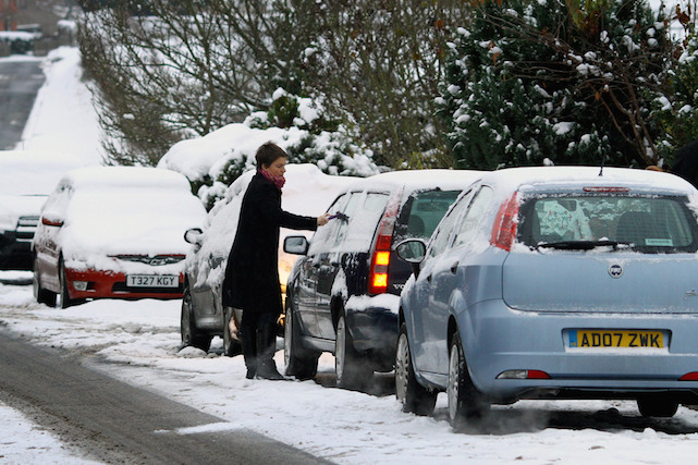 A member of the public de-ices their car near Ashford, Kent, as large areas of Britain were brought to a halt today as the big freeze tightened its grip on the nation.