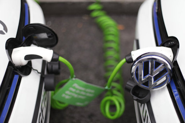 A pair of Zipcar club car-sharing Volkswagen Golf GTE plug-in petrol-electric hybrid cars being recharged on a street in central London.