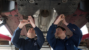 Guys working on a car