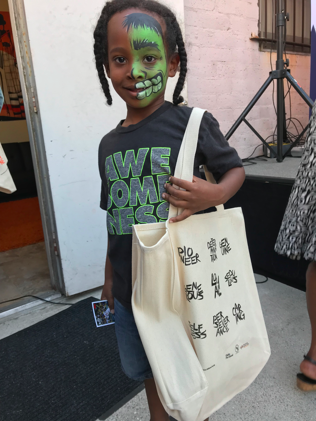 Girl wearing facepaint holds a bag.