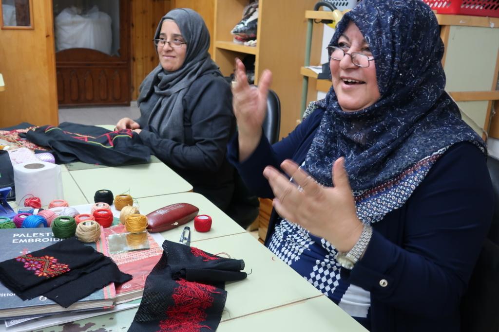 パレスチナ刺繍はアトファルナの人気の職業訓練のひとつ。カバジャ所長の挨拶に手話で応える女性。名刺入れなどの小物からクッションカバーやロングドレスまで、彼女たちの手によって様々な作品が仕上がっていく