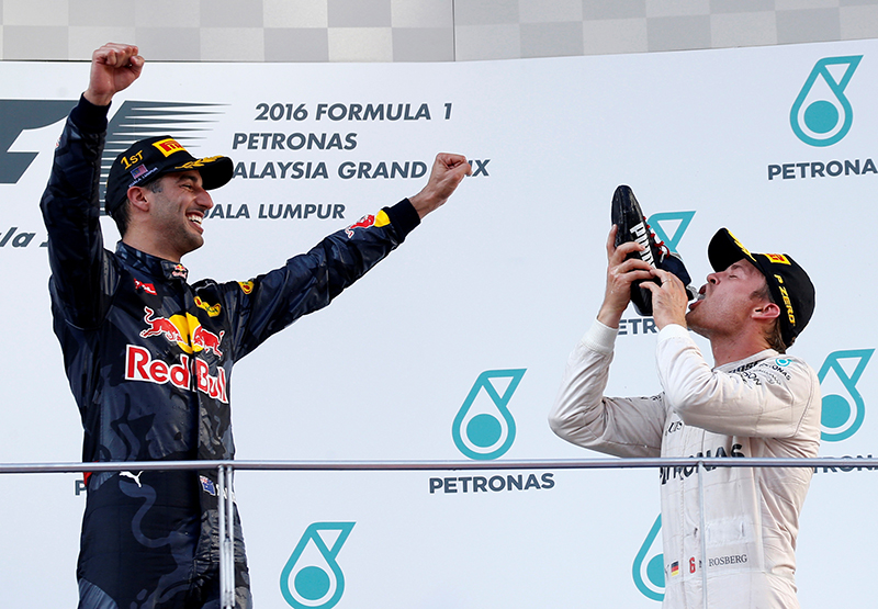 Red Bull's Daniel Ricciardo of Australia makes Mercedes' Nico Rosberg of Germany drink from his shoe as they celebrate on the podium.