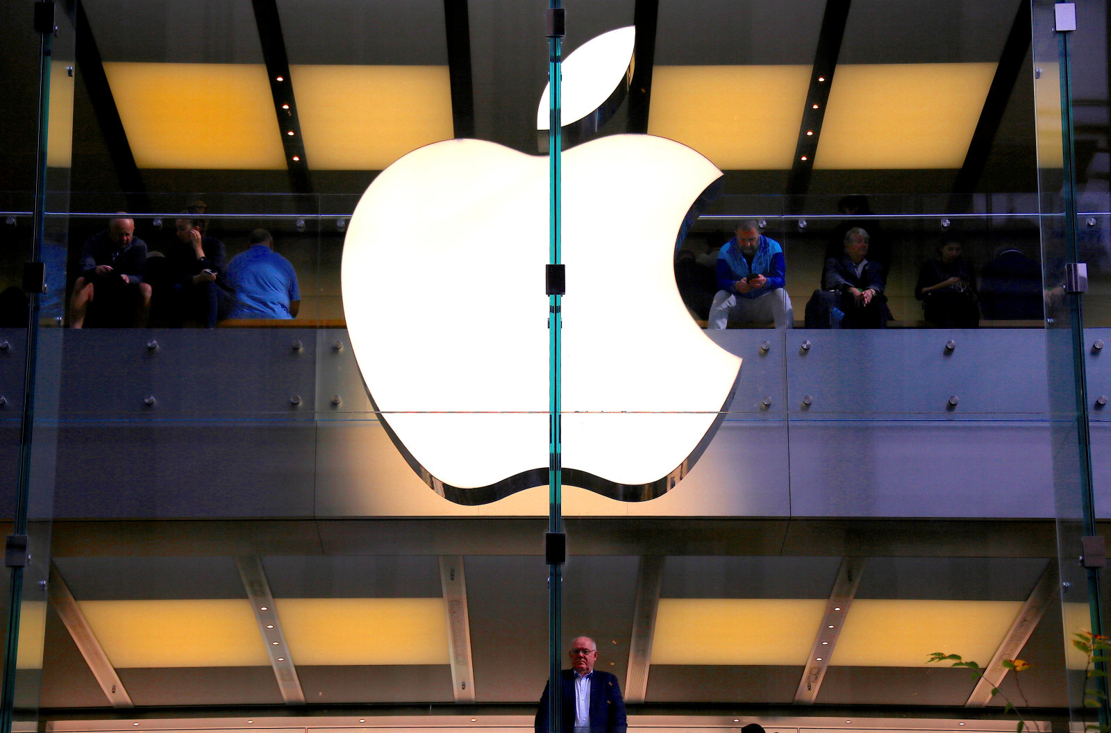 A customer stands underneath an illuminated Apple logo as he looks out the window of the Apple store located in central Sydney, Australia, May 28, 2018. REUTERS/David Gray     TPX IMAGES OF THE DAY