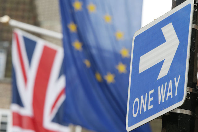 A 'one way' road traffic sign is juxtaposed with the Union Jack and the EU flag hanging outside Europe House in Smith Square, London. PRESS ASSOCIATION Photo. Picture date: Friday March 10, 2017. Photo credit should read: Yui Mok/PA Wire