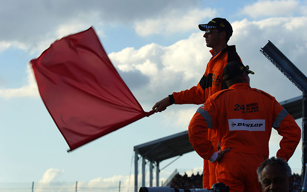 A marshall waves a red flag at the 2014 24 Hours of Le Mans.
