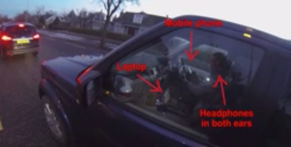 Man caught using laptop, mobile phone and headphones while driving (video)