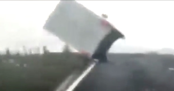 Moment lorry is blown over in 70mph winds (video)