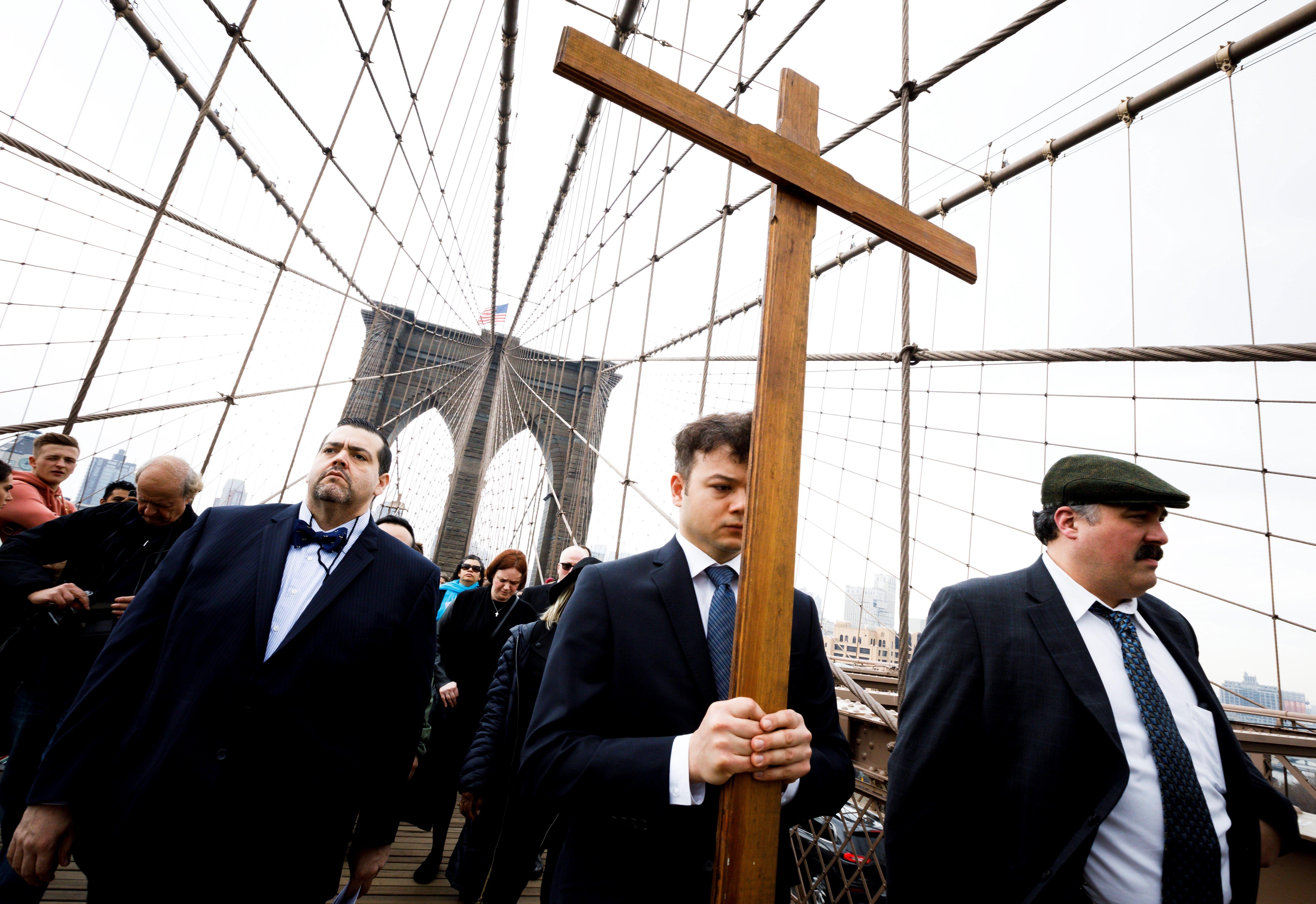 Vladimir Kuzman porta una cruz de madera por la 23 celebración anual del Vía Crucis sobre el Puente de...