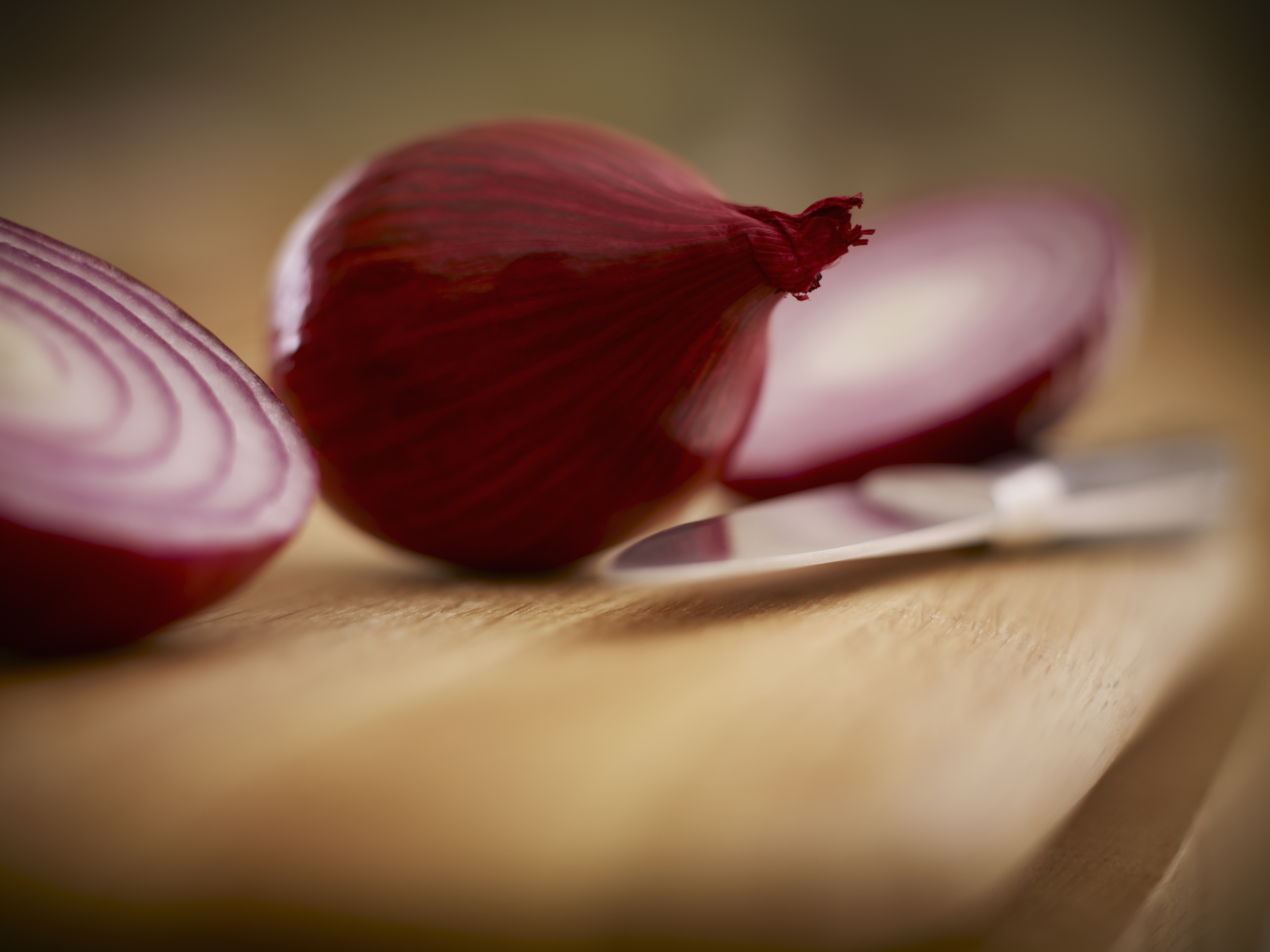 Close up of red onions and knife on cutting board